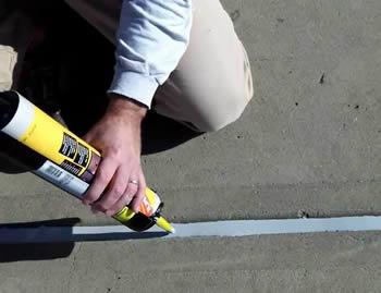 A person is squeezing the sealant into a concrete joint with a caulking gun.