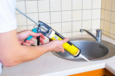 A person is gluing hand washing sink with a caulking gun.