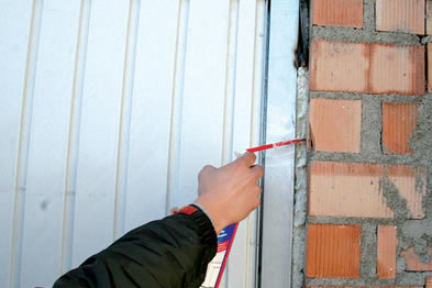 A person is squeezing the sealant into the joint between wall and door.