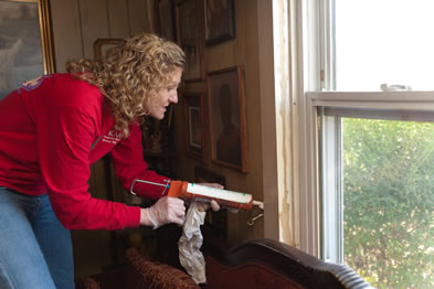A woman is squeezing the sealant into the joint between window and wall.