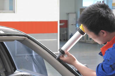 A man is squeezing the sealant into the joint of automobile windscreen with a caulking gun.